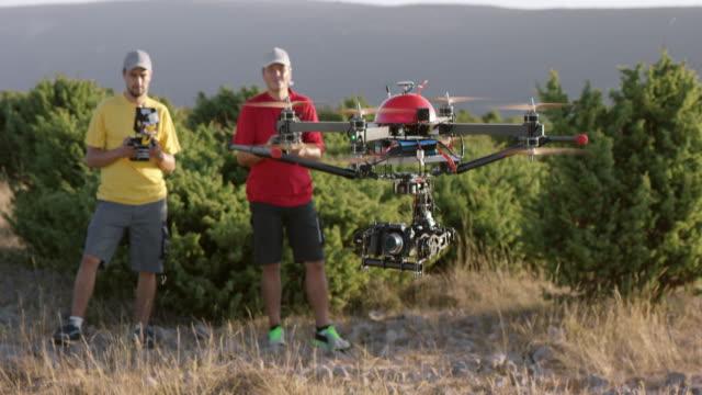 slo mo airborne drohne von zwei piloten gesteuert - fernbedienung stock-videos und b-roll-filmmaterial
