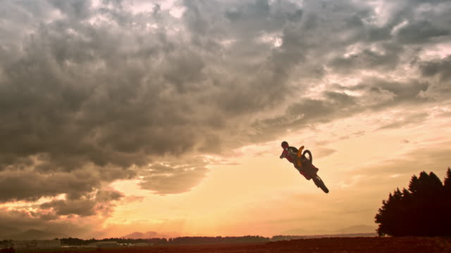 slo mo airborne motocross rider at sunset - sporting term stock videos & royalty-free footage