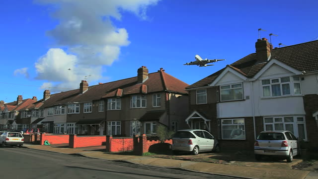 aircraft approaching airport flying low over residential houses, causing continuos noise and pollution. west london on heathrow approach flightpath. - approaching stock videos & royalty-free footage