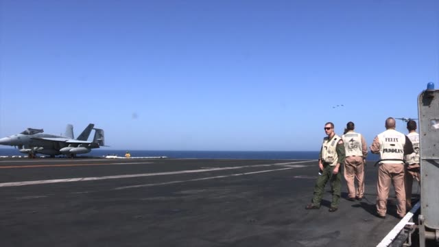 Aircraft are directed around the flight deck of USS George HW Bush and onto catapults to be launched