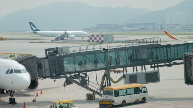 vídeos de stock e filmes b-roll de aircraft arrival with gangway and passenger walking to airport terminal - pista de aterragem