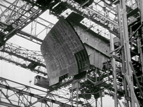 stockvideo's en b-roll-footage met aircraft carrier enclosed in scaffolding w/ crane moving behind buildings ha ws crane moving along dock ws men working on deck assembly ms person... - 1943