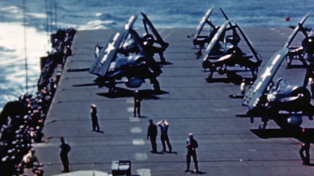 aircraft carrier flight crew on deck beside row of tbm avengers with wings folded, and gunners manning carrier's 20mm and 40mm gun positions underway... - pacific war video stock e b–roll