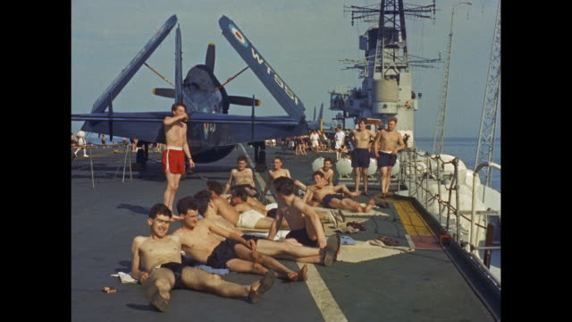 stockvideo's en b-roll-footage met aircraft carrier hms victorious - men relaxing on flight deck in the sun - matroos