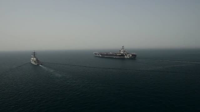 stockvideo's en b-roll-footage met aircraft carrier uss theodore roosevelt transits the arabian gulf alongside the arleigh burke-class guided-missile destroyer uss higgins . theodore... - perzische golf