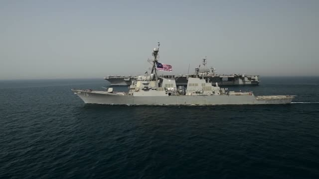 stockvideo's en b-roll-footage met aircraft carrier uss theodore roosevelt transits the arabian gulf alongside the arleigh burke-class guided-missile destroyer uss higgins . theodore... - oorlogsschip