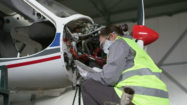 flugzeugingenieur inspiziert flugzeugtriebwerk in einem flugzeughangar, bevor er wieder in den flug. - luftfahrzeug stock-videos und b-roll-filmmaterial