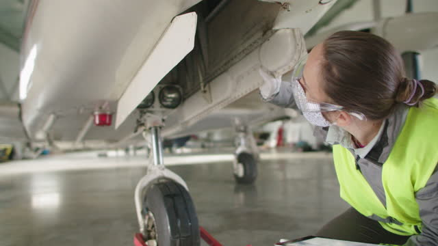 aircraft engineer inspecting aircraft engine in an airplane hangar before putting it back to flight. - air vehicle stock videos & royalty-free footage