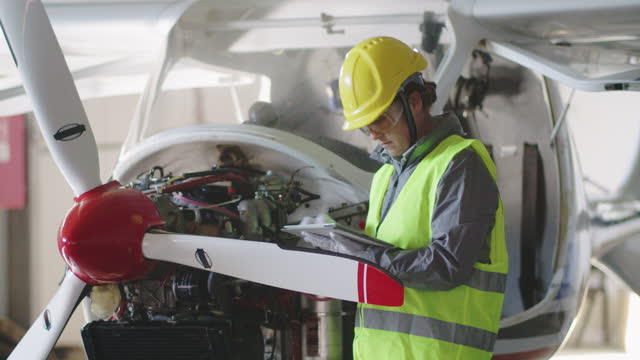 aircraft engineer inspecting aircraft engine in an airplane hangar before putting it back to flight. - genderblend stock videos & royalty-free footage