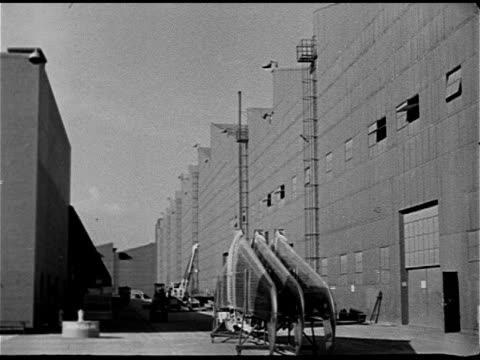Aircraft factory field w/ many aircraft Parts being wheeled between buildings possibly hangars HA WS Shipyard w/ scaffolding cranes Worker using...
