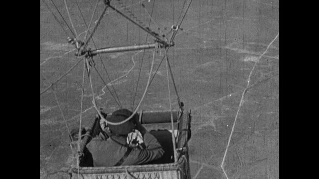 aircraft flying around observation balloon in the sky / low level aerial shot of arras railway station and surroundings / cs of observer in gondola... - artiglieria video stock e b–roll