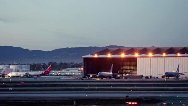 WS T/L Aircraft hangars and runways at dusk, LAX airport / Los Angeles, California, USA