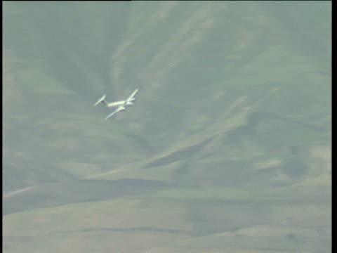UN aircraft in flight above remote runway in barren mountainous landscape Afghanistan