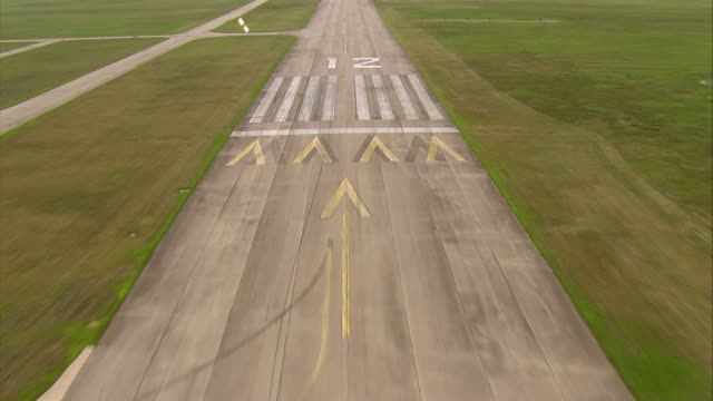 Aircraft POV landing on runway in a green field in a municipal airport.