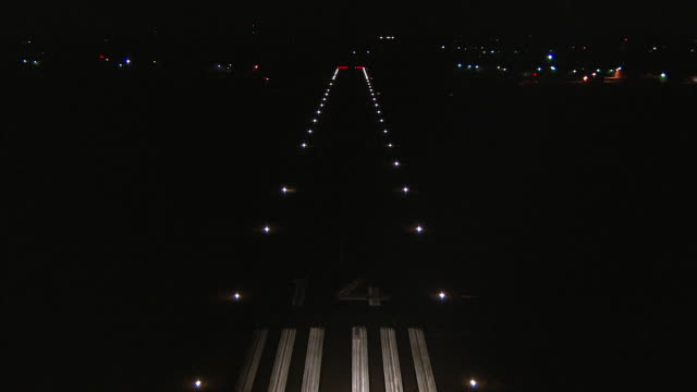 Aircraft POV landing on runway outlined in red, blue and white lights at night.