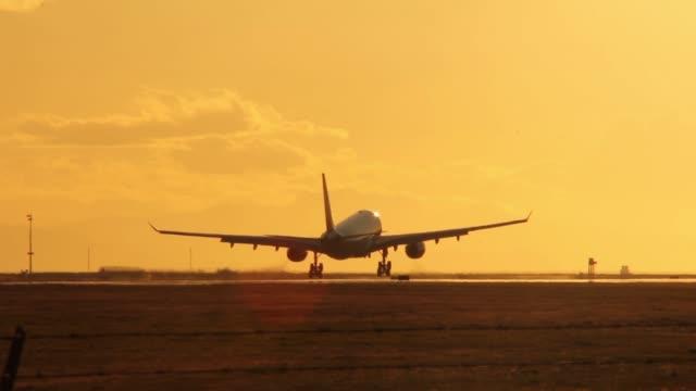 a310 aircraft landing on runway with yellow sunset sky - landefahrwerk stock-videos und b-roll-filmmaterial