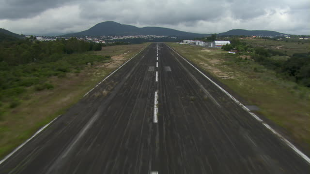 Aircraft POV landing then ascending again on runway in small rural airport in Mexico City.