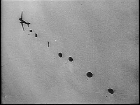 aircraft leave contrails in sky / wide shot footsoldiers walk in long line over dunes / planes fly and parachutes fill sky / paratroopers deploy from... - 1944 stock videos & royalty-free footage