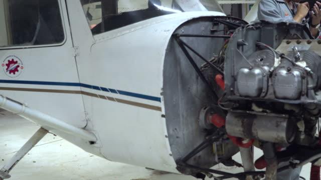 vídeos de stock, filmes e b-roll de manutenção de aeronaves pelo jovem engenheiro ou técnico inspeciona motor de jato do avião - veículo aéreo