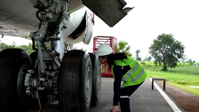 vídeos y material grabado en eventos de stock de los ingenieros de mantenimiento de aeronaves analizan, inspeccionan y trabajan con ruedas de aeronaves. - vehículo aéreo