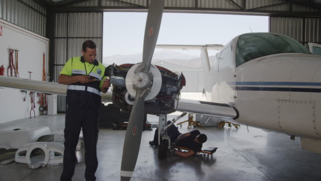 TS WS aircraft mechanics working on engines and landing gear of twin engine propeller aircraft in hangar, RED R3D 4K