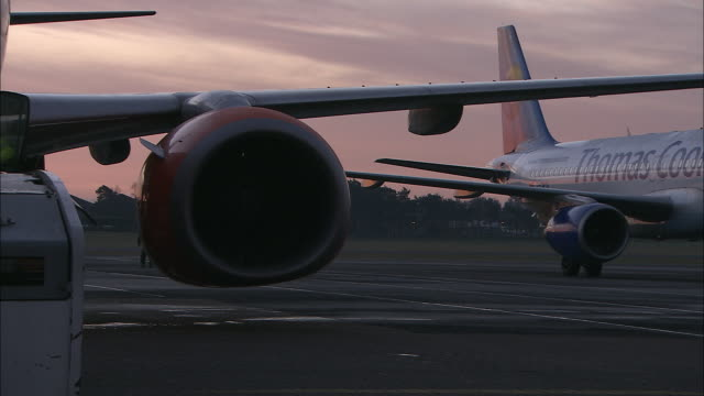 ms aircraft moving back on tarmac at dawn, wing and engine in foreground, belfast airport, ireland, united kingdom - belfast stock videos & royalty-free footage