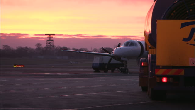 vídeos de stock e filmes b-roll de ms aircraft on tarmac at dawn, fuel truck in foreground, belfast airport, ireland, united kingdom - belfast