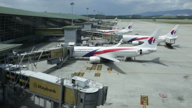 aircraft operated by malaysian airline system bhd stand on the tarmac at kuala lumpur international airport in sepang malaysia ground staff load an... - malaysia stock videos & royalty-free footage