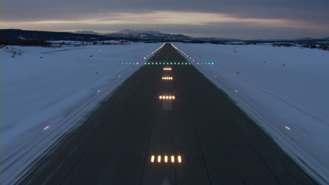 Aircraft POV over strobe lights leading to runway at Erik Nielsen Whitehorse International Airport at dusk.