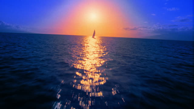 aerial aircraft point of view low over ocean toward + over sailboat / orange glowing halo around sun / hawaii - sailing boat stock videos & royalty-free footage