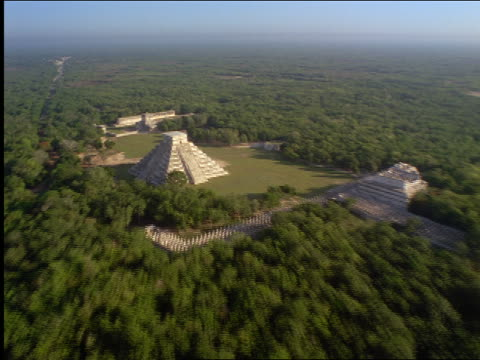 aerial aircraft point of view over chichen itza pyramid temple ruins surrounded by forest / yucatan, mexico - chichen itza stock videos and b-roll footage