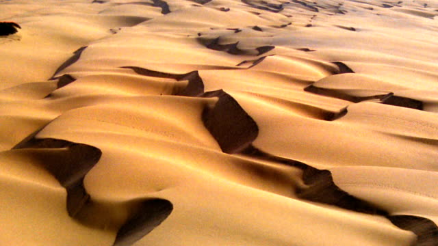 vidéos et rushes de aerial aircraft point of view over desert + sand dunes - aride