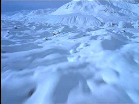 AERIAL aircraft point of view over snow-covered rocky tundra toward mountains / Alaska