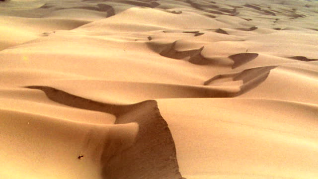 AERIAL aircraft point of view zoom in over desert + sand dunes