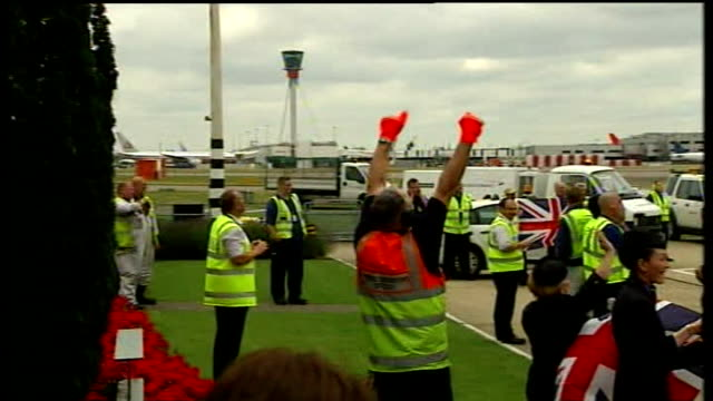 BA aircraft taxiing Airport staff and BA flight attendants cheering outside terminal and waving Union Jack flags Rebecca Adlington and Chris Hoy...