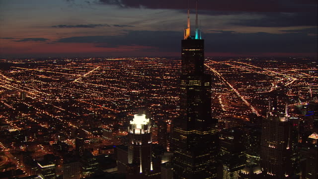 AERIAL aircraft POV toward and past 311 South Wacker, Sears Tower, and AT&T Corporate Center at dusk / downtown Chicago, Illinois.