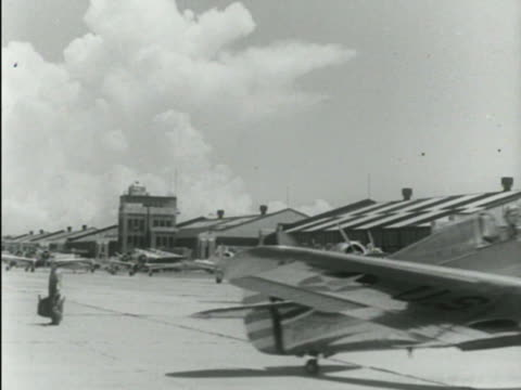 w/ unidentified GHQ plane w/ dark fuselage light wings taxiing through frame DC3 parked in front of hangar BG Angled WS Line of Boeing model 299...