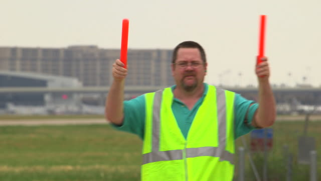 Airfield ground control worker directing aircraft with plane taking off background/DFW International Airport, Dallas-Fort Worth, Texas, USA