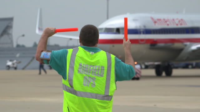 vídeos de stock e filmes b-roll de airfield ground control worker directs jetliner on tarmac/dfw international airport, dallas-fort worth, texas, usa - alfalto