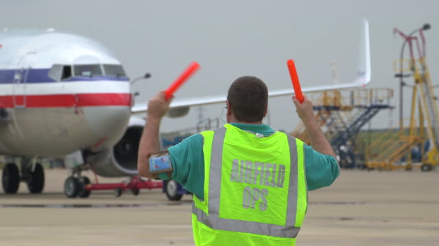 vidéos et rushes de airfield ground control worker directs jetliner on tarmac/dfw international airport, dallas-fort worth, texas, usa - montrer la voie