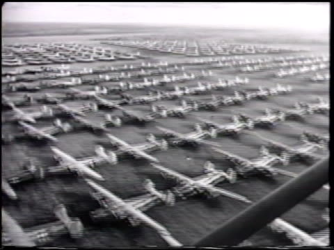 airfield w/ wwii aircraft parked in sections b24 'liberator' heavy bombers below passing douglass c47 'skytrain' transports martin a30 'baltimore' w/... - passing a note stock videos and b-roll footage