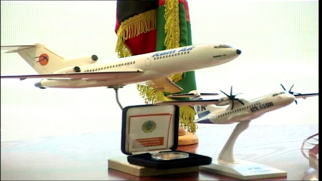 vidéos et rushes de airline business; int kamgar working at his desk close shot of kam air model plane on stands passengers buying airline tickets kamgar chairing... - président d'organisation
