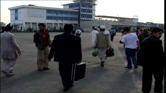 passengers disembarking from kam air plane ground crew member guiding plane on runway passengers queuing to board plane afghanistan cricket team... - cricket team stock videos and b-roll footage