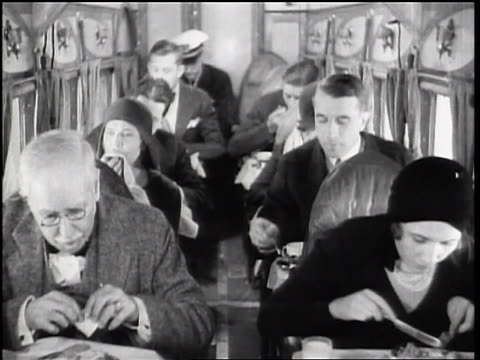b/w 1928 airline passengers eating in their seats in cramped airplane cabin - 1928 stock videos & royalty-free footage