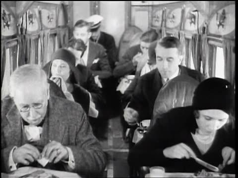 vídeos y material grabado en eventos de stock de b/w 1928 airline passengers eating in their seats in cramped airplane cabin - 1928