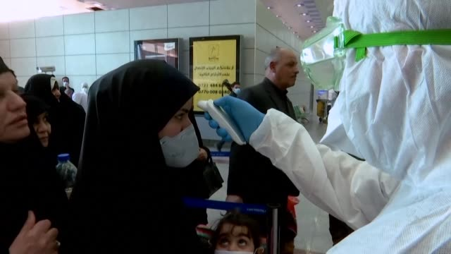 airline passengers wearing masks and arriving to iraq from iran have their temperatures taken by medical teams in protective outfits at najaf and... - najaf stock videos & royalty-free footage