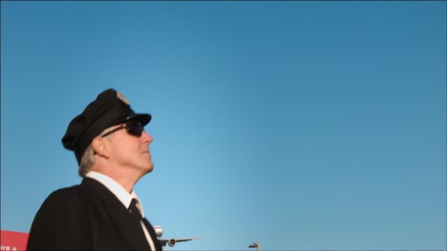 m/s airline pilot steps into frame, airplane passes overhead: ana boeing-777 - endast en medelålders man bildbanksvideor och videomaterial från bakom kulisserna