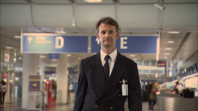 ms ts airline pilot walking through airport/ munich, germany - pilot stock videos & royalty-free footage