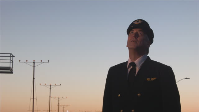 M/S airline pilot watches as airplane passes overhead, early evening