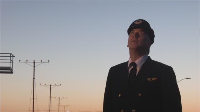 vidéos et rushes de m/s airline pilot watches as airplane passes overhead, early evening - pilot